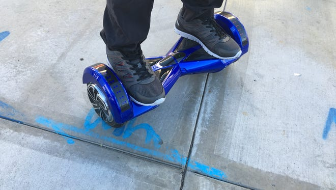 A Manhattan Beach man rides around town on a multi-colored hoverboard, a stand-up, motorized scooter.