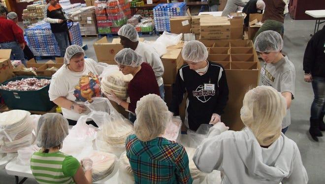 Volunteers repack pizza crusts.
