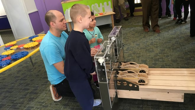 Mid-Hudson Children's Museum Director of Exhibits Joe Cook assists museum visitors as they launch cars in the new Raceways exhibit in The Science Center @ MHCM.