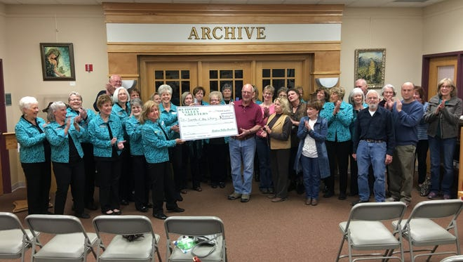 Ruidoso Valley Greeters, in turquoise, present a check for $4,000 to the Friends of the Ruidoso Library.