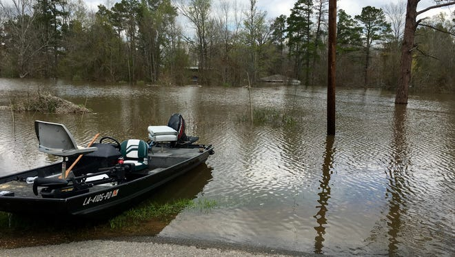 A boat rests on the side of Highway 500 east of Georgetown in Grant Parish not far from a flooded home Sunday. Sheriff's deputies and some residents took to boats to check on houses in flooded areas across the parish.