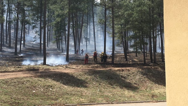 Fire crews take a breather during work on smoky ground that just hours earlier looked like a threatening line of flames at the edge of Ruidoso High School property.