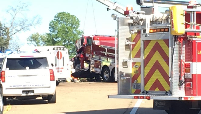 A wrecker helps lift a fire truck off the car with which it collided Sunday.