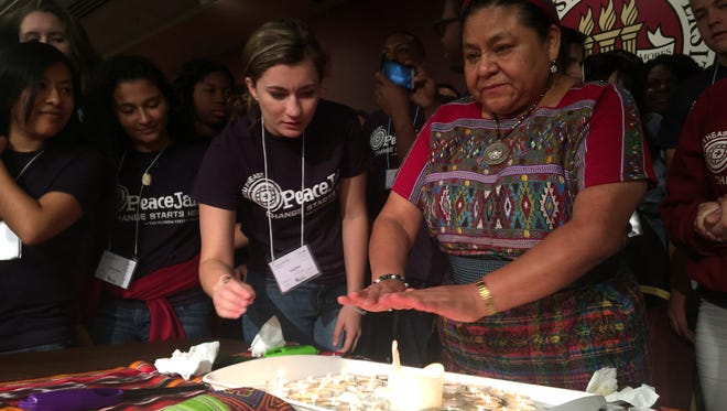 Nobel Peace Prize Laureate Rigoberta Menchú Tum, FSU senior Leah Sutter and several other mentors surround the sacred fire, lit during PeaceJam's Ceremony of Inspiration.