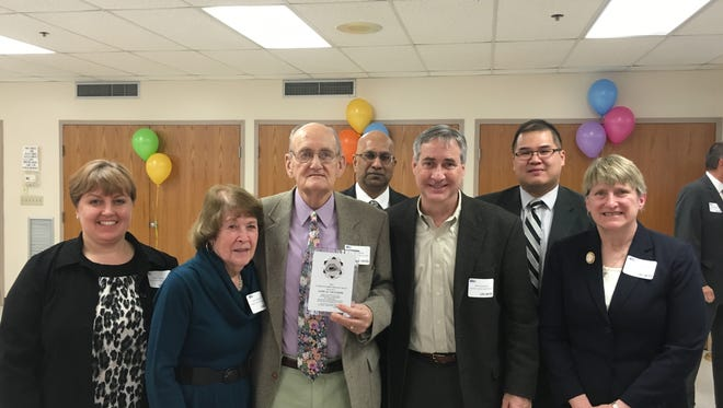 Sam Gillespie, center, holds his 2016 Cindy Hawbaker Memorial Award from United Way of Franklin County while standing with, from left, Gloria Keener, executive director of Franklin County Legal Services; Carol Gillespie; Mahesh Rao, founding Executive Director of FCLS; Phil Cosentino, FCLS Board President; Lam D. Truong, FCLS Managing Attorney; and Ellen Gigliotti, President of Franklin County Friends of Legal Services.