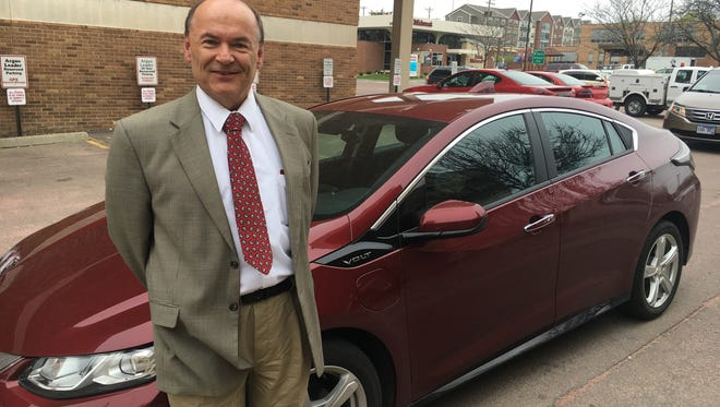 Jay Williams, Democratic candidate for U.S. Senate, poses in front of his electric car.
