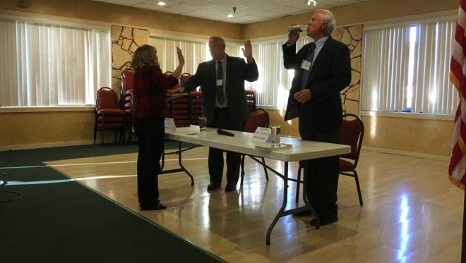 """Municipal Judge Beverly Rankin pretends to swear in 12th District Judge Dan Bryant and challenger Chris Nedbalek """"under penalty of perjury"""" before a candidate forum Monday."""