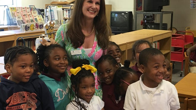 Kimberly Baker, president of Junior League Montgomery, stands with students at Chisholm Elementary School on Thursday, May 19, 2016, after their school was presented with a $5,000 check from JLM for new library books.
