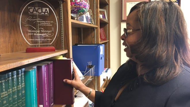 Prosecuting attorney Monique Metoyer pulls a law book from the shelf. Metoyer oversees 800-900 misdemeanors and 150-plus felony cases.