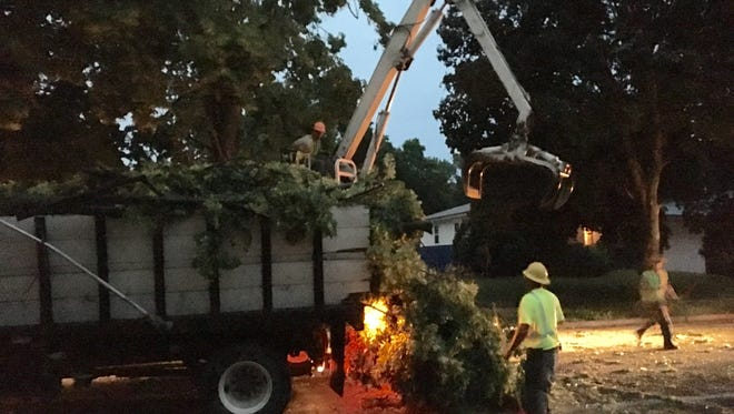 Crews clean up a large tree that fell at 13th and Bahnson in Sioux Falls Friday night after high winds knocked it on the road.