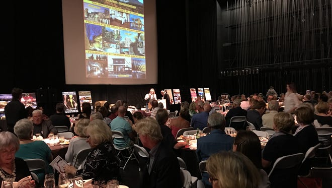 Auctioneer Steve Talbot asks for bids on a helicopter junket and tour of luxury inns during the Taste of the Spencer Saturday.