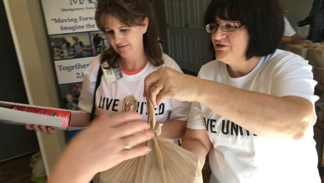 "Pam Goodwin, right, director of senior services at Montgomery Area Council on Aging, hands out bags of frozen meals to volunteers during the United Way ""Day of Action"" on Tuesday, June 21, 2016."
