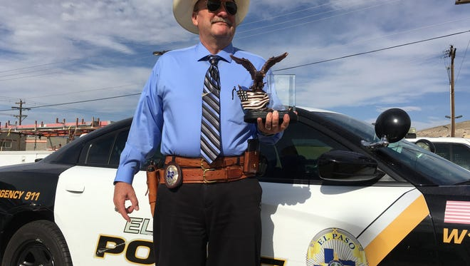 El Paso Police Department Detective Michael Aman, who is currently the lead cold case investigator for the department, poses with the 2016 Officer of the Year award presented to him by the El Paso Chapter of the Military Order of the World Wars.