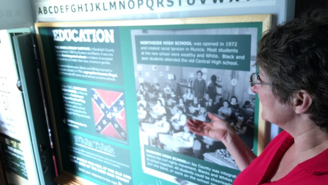 Beth Messner points out a display aboard the MLK Dream Team's Freedom Bus.
