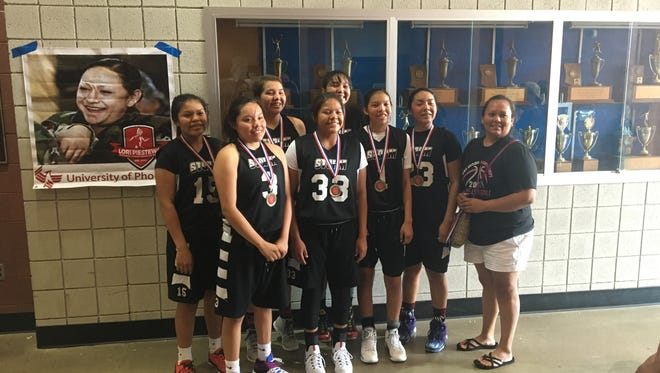 Jacqulynn Nakai (3, second from left) and Tia Woods (15, far left) pose after winning the girls high school basketball division at the Lori Piestewa National Native Games Sunday, July 17, at Fountain Hills High.