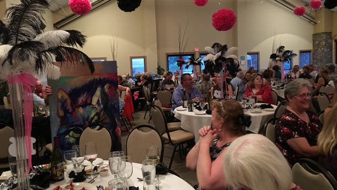 Attendees at the Furr Ball Tuesday evening consider an original portait of a wolf during the event's live auction.
