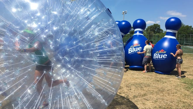 Carly Herweyer, 37, of Northville, competes in a human hamster ball July 23, 2016 during the Labatt Undomesticated Games on Belle Isle.