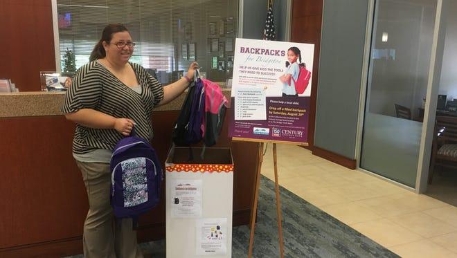 Gisela Negron, a representative of Century Savings Bank, accepts a donation for the Backpacks for Bridgeton program.
