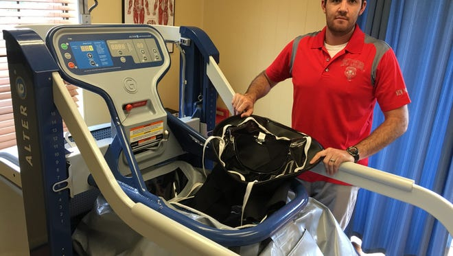 Paul Regalado of Therapy Associates displays the special shorts and pressurized treadmill that lets users exercise while putting only a fraction of their body weight on legs and joints.