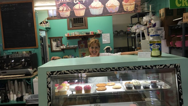 Maria Cottom of Nana's Yummy Cupcakes stands behind the merchandise that makes customers dig deep for their last pennies.
