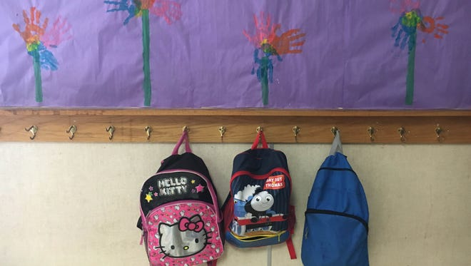 Backpacks hanging in an elementary school classroom.