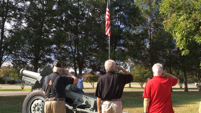 VFW Post 1848 members salute the American flag flying at half-mast during a Sept. 11 memorial service on Saturday.