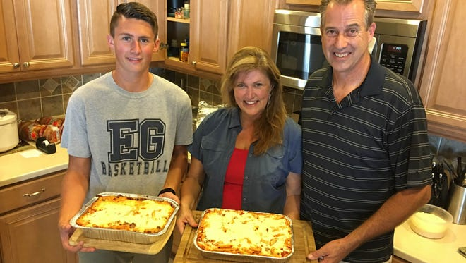Max Yesowitch, Deborah Metz and Bruce Metz show off a sample of her 'firehouse ziti' delivered to area first responders for Sept. 11.