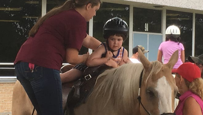 Sarah Milburn helps Bryce Beck, age 5, off of a pony, on Saturday at the Autism Awareness Fair at Chambersburg Area Middle School South.