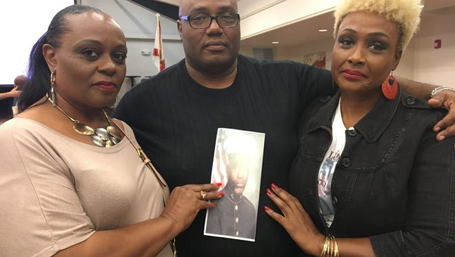 Veronica Jones-Greene, Kevin Jones and Melissa Jones pose with a picture of their brother Keith Jones. Keith was killed in Fort Myers almost 20 years ago and his homicide remains unsolved.
