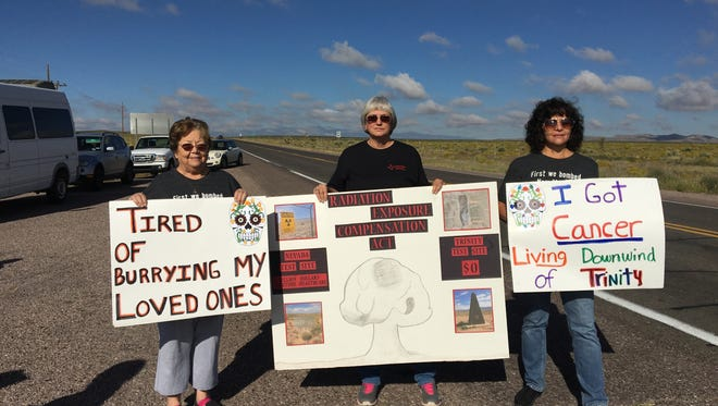 Tularosa Downwinders protesters (l-r) Rosalie Cordova, Laura Greenwood, and Tina Cordova display signs at the Stallion Gate to the Trinity site Saturday.