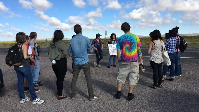 Tina Cordova, with sign, co-founder of the Tularosa Basin Downwinders, talks to a group of University of New Mexico students about what radiation from the first atomic blast did to New Mexico residents downwind.