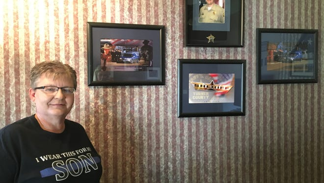 Sandy Mechels' son Chad Mechels died performing a well-being check near Marion, SD, in 2009. Here she has a wall honoring his memory in her home.