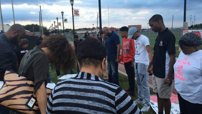 Students and activists gathered to protest at North Central High School after social media posts showed students posing with the Confederate flag. The protest, organized by NCHS senior Nicodemus Monts, second from right, ended with a prayer.