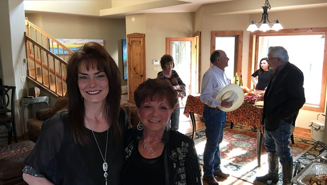 Sisters Shanna Flaherty, left, and Montie Carol Madera smile as guests arrive for Business After Hours at their sixth luxury visitor rental home.