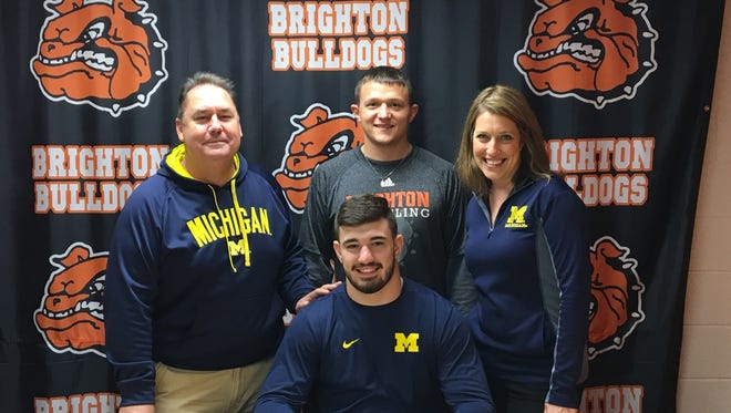 Brighton's Luke Ready (center)sits with his parents and coach Tony Greathouse (back center) as he signs his letter of intent to wrestle at Michigan.