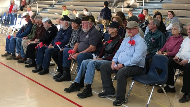 Ruidoso area military veterans wait for Ruidoso Middle School students to assemble for a ceremony honoring them Friday.