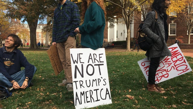 Student anti-Trump protesters, including Jacob Morales (right), a senior from Elsmere, gather at the  Green at the University of Delaware Tuesday.