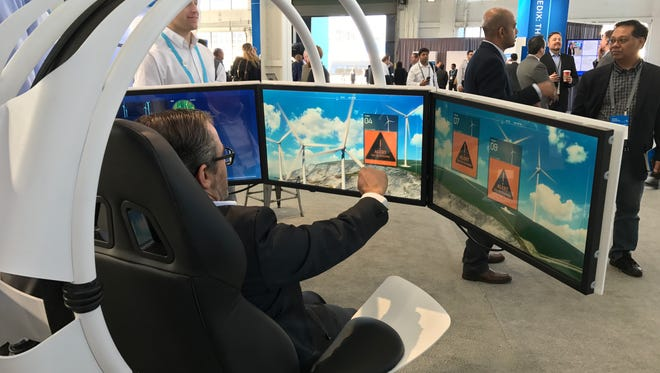 A visitor to GE's Minds + Machines event tries out a Web-connected platform that offers real time operational status updates on wind farm turbines.