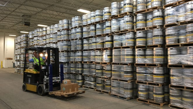 A Bell's Brewery employee drives a forklift Sept. 22, 2016 by stacks of kegs in Comstock.