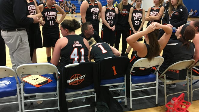 Marine City girls basketball coach Jeff Austin speaks to his players during a basketball game.