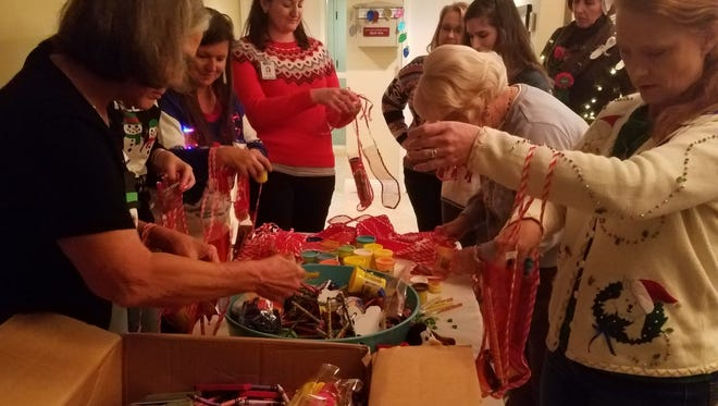 United Way's Women's Leadership Council stuffed stockings for four-year-olds and celebrated with tacky holiday sweaters.