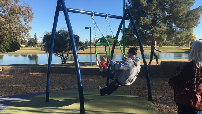 A mother and her young son ride the toddler expression swing at Dobson Ranch Park in Mesa on Dec. 3, 2016. The park is for children of all abilities.