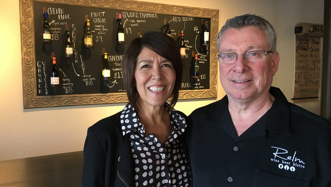 RELM Wine & Beer Bistro owners Valeri and Patrick Mervyn pose with the wines-by-the-glass chalkboard at the Camarillo business.