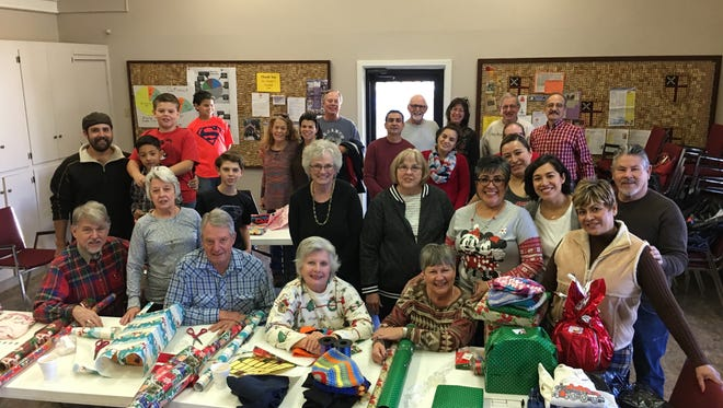 Volunteers gather at the Episcopal Church of the Holy Mount Saturday to wrap presents for 45 local families in need.