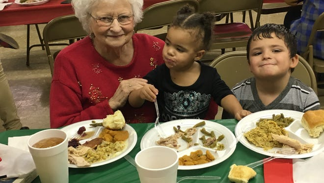 Billie Kupatt and her great-grandchildren, Isaiah Hernandez, 6, and Honnor Malone, 2, enjoy the Christmas day dinner at St. John's United Methodist Church in Stamford. The meal is a family tradition for the Kupatt clan.