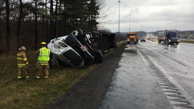Washington Township firefighters look at an overturned semi truck near exit 169 of I-71 south on Monday, Dec. 26, 2016. The driver experienced a medical emergency while driving and tried to pull off the roadway but rolled the truck.
