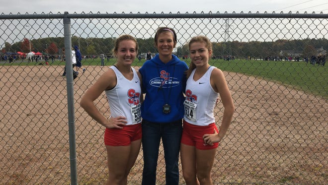 St. Clair cross country coach Jennifer McDonald stands with Morgan Markel and Gabrielle Morton after the Saints won the regional at Anchor Bay High School.
