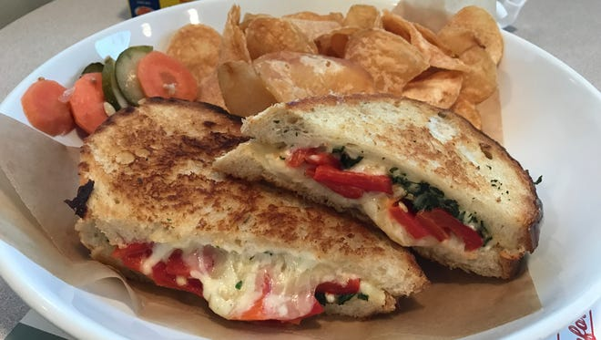 A caprese grilled cheese, served with Old Bay chips and roasted vegetables.