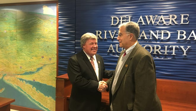 Incoming DRBA Executive Director Thomas Cook shakes hands with his predecessor Monday at the authority headquarters.