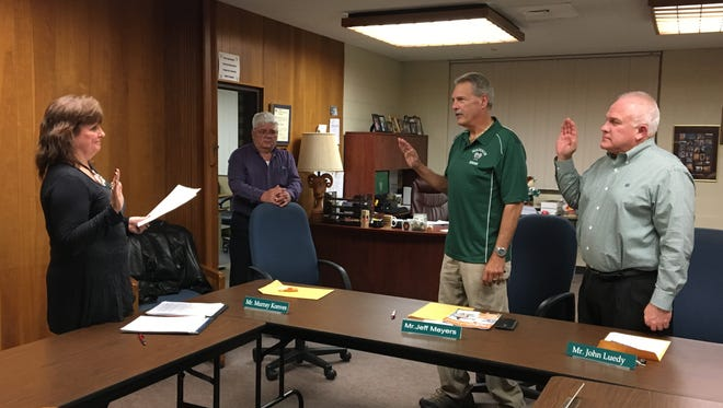 Robin Klenk swears in Jeff Meyers, left, and John Luedy, right, as president and vice president, respectively, of the Madison Local Board of Education on Wednesday, Jan. 11, 2017. Board member Murray Konves stands in the background.